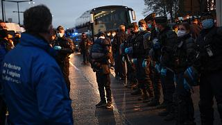 Migrants wait to be evacuated by Gendarmerie forces at a makeshift camp set below the motorway in Saint-Denis, France, on Nov. 17, 2020.