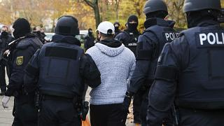 Police officers escort a person for an identity check in Berlin, Germany, Tuesday, Nov. 17, 2020.