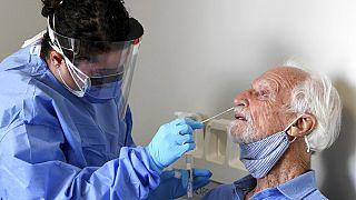 ممرضة تقوم بمسحة أنف لإجراء اختبار كوفيد-19