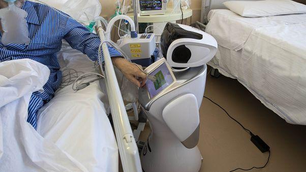 مصاب بكوفيدـ19 يستعمل شاشة روبوت داخل وحدة للعناية المركزة في إيطاليا. 2020/04/08