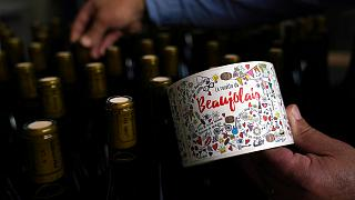 Tuesday, Nov. 12, 2019, a man picks a bottle of Beaujolais Nouveau in the Vinescence cellar in Saint Jean d'Ardieres, in the Beaujolais region