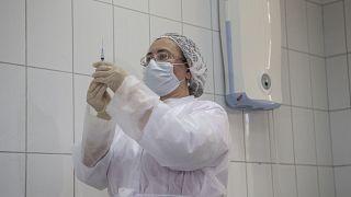 Медсестра готовится к введению экспериментальной вакцины или плацебо волонтёру