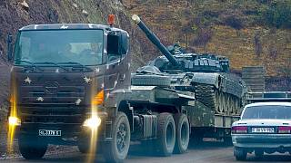 A truck carries an Armenian tank during the withdrawal of Armenian troops near the border between Nagorno-Karabakh and Armenia, Friday, Nov. 13, 2020.