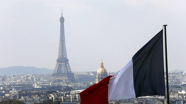 The French flag above the skyline of the French capital with the Eiffel Tower.