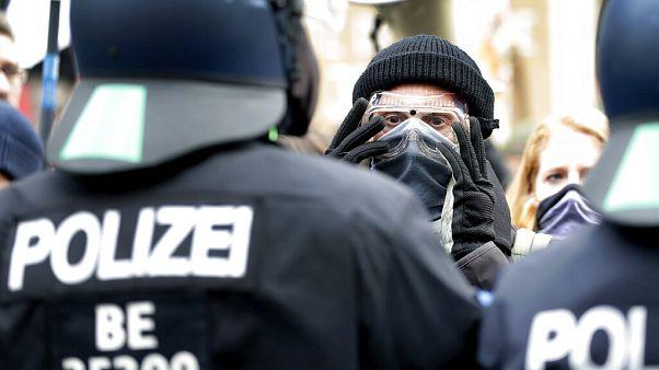 Manifestante ajusta máscara de gás em frente a agente da polícia