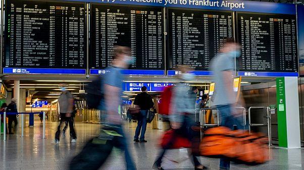 ركاب يمشون بمطار فرانكفورت، ألمانيا.