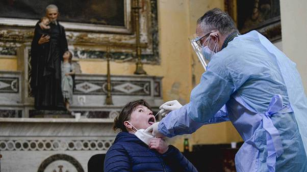 A medical operator performs COVID-19 test swabs in the Church of San Severo Outside the Walls, in the heart of Naples, Italy, Wednesday, Nov. 18, 2020.