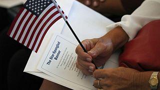 یک نامزد شهروندی با در دست داشتن پرونده خود و پرچم آمریکا در انتظار شروع مراسم اعطای تابعیت است
