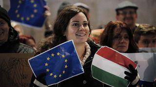 Együtt az EU-s és a magyar zászló egy demonstráló kezében (illusztráció)