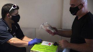 Dorme negli aeroporti vuoti e riparte subito dopo la consegna per evitare la quarantena: Mishel Zrian, corriere israeliano (a dx) riceve il midollo osseo da trasportare.