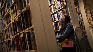 A woman wears a face mask, to protect against the spread of coronavirus, as she browses for books in a second-hand bookshop in Brussels, June 11, 2020.