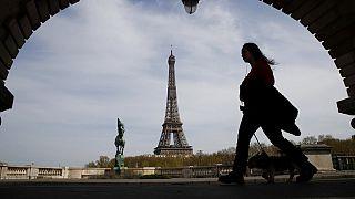 Archivo. Una mujer pasea a su perro cerca de laTorre Eiffel de París.