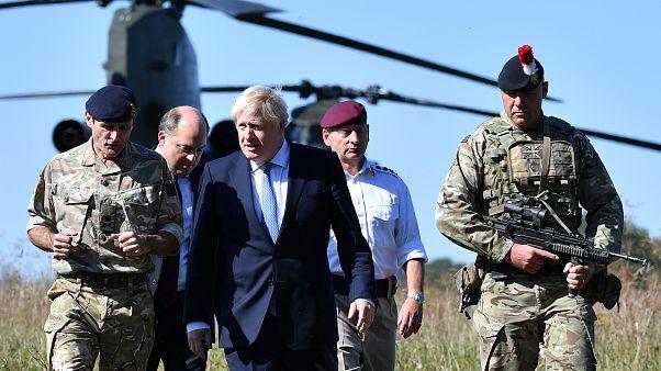 بوريس جونسون  مع وزير الدفاع البريطاني بن والاس في منطقة تدريب سهل سالزبوري بالقرب من سالزبوري، جنوب غرب إنكلترا
