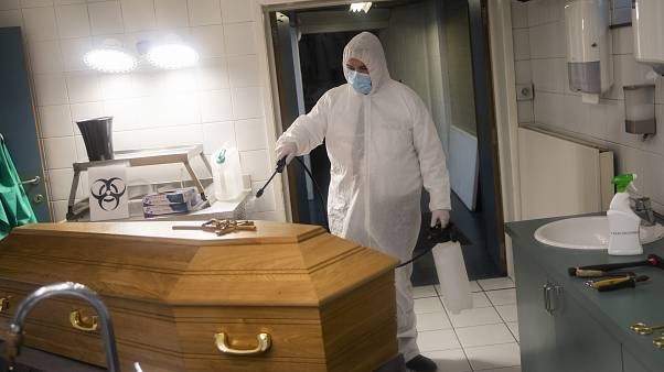 A worker, wearing a full protective equipment, disinfects the casket of someone who died of coronavirus COVID-19 at a funeral home in Charleroi, Belgium, Nov 17, 2020.
