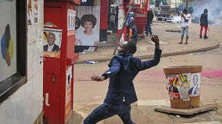 A person prepares to throw a rock during clashes between security forces and protesters supporting opposition presidential candidate Bobi Wine