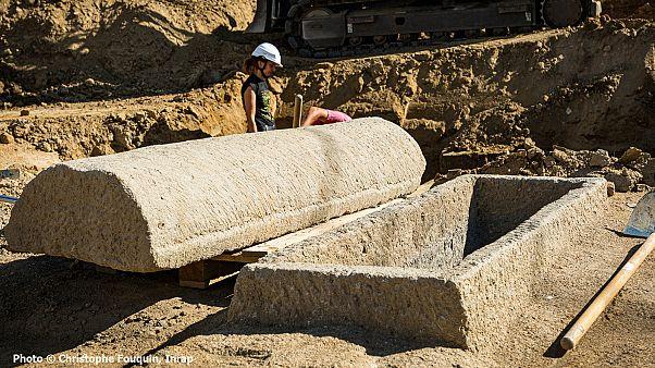 Sarcophage en pierre ouvert, le couvercle est posé à côté de la cuve