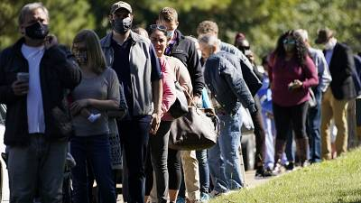 Voters brave a bright sun as they wait to cast their ballots in Mississippi, US.
