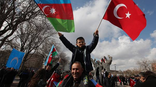 Un bambino turco sventola la bandiera della Turchia e dell'Azerbaijan
