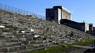 People sit on stairs at the 'Zeppelinfeld' besides the main tribune of the 'Reichsparteigelande' (Nazi Party Rally Grounds) in Nuremberg, Germany, Wednesday, Nov. 18, 2020.