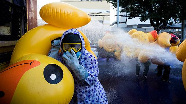 Protesters take cover with inflatable ducks as police fire water cannon during an anti-government rally near the parliament in Bangkok, Thailand. November 17, 2020