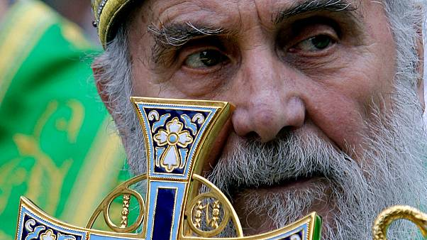 In this May 24, 2012, file photo, Serbian Orthodox Church Patriarch Irinej holds a cross during a procession marking Belgrade's patrons saint day, Spasovdan, in Belgrade
