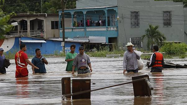 Hombres caminan por una calle inundada después del paso del huracán Iota en La Lima, Honduras