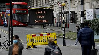 A sign is displayed outside London's Waterloo train station to remind people thy are required to wear face coverings inside the station