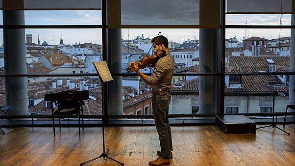 A musician in a face mask plays the violin at a rehearsal at the Teatro Real in Madrid, Spain, Friday, November 13, 2020.