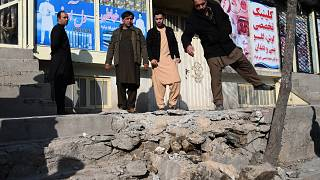 Residents gather at a site after several rockets land at Khair Khana, north west of Kabul.