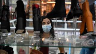 A woman looks at a store window advertising Black Friday discounts at a shopping centre in Caracas, Venezuela.