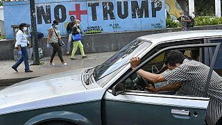 یک شهروند ساکن کاراکاس خودروی خود را که بنزینش تمام شده، هل میدهد