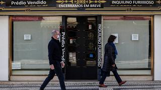 Traseuntes passam por uma loja fechada na zona da baixa pombalina de Lisboa