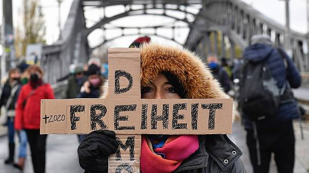 """A woman attending a silent march against measures to curb the spread of coronavirus holds a cross reading """"Freedom democracy"""" in Berlin on November 22, 2020."""