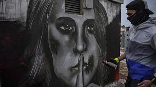 لوحة غرافيتية على سطح مبنى في أثينا، امرأة مصابة بجروح في وجهها وإصبعها على شفتيها، مستوحاة من زيادة حالات العنف المنزلي