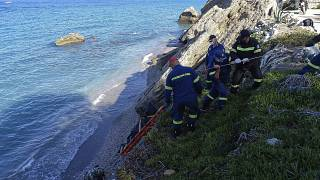 Firefighters retrieve the body of a migrant from the beach after the boat partially sank near the Greek island of Rhodes.