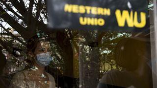 Una mujer espera para recoger dinero en una oficina de Western Union en su último día de actividad en La Habana, Cuba, el 23 de noviembre de 2020.