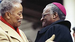 Mayor David Dinkins, left, gets a hug from South African Bishop Desmond Tutu