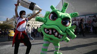 Koronavírus elleni védőoltásnak és koronavírusnak öltözött színészek egy tüntetésen Limában