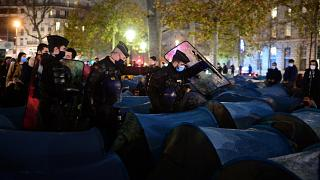 Police forcefully dismantle a refugee camp in central Paris.
