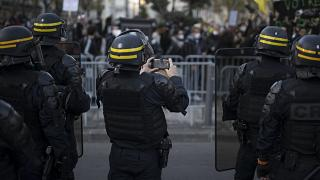A French riot police officer photographs protesters with his phone during a demonstration in Marseille, southern France, Saturday, Nov. 21, 2020.