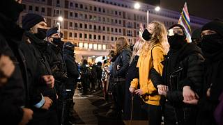 Protesters face a line of police officers during a demonstration against a top court ruling restricting abortions in Warsaw, Poland, Wednesday, Nov. 18, 2020.