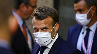 French President Emmanuel Macron, center, leaves the European Council building in the early morning during an EU summit in Brussels, Monday, July 20, 2020