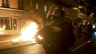 Francia rendőr egy égő barikád mellett Párizsban, 2020. november 24-én
