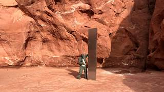 A state worker inspects a metal monolith found in a remote area in Utah