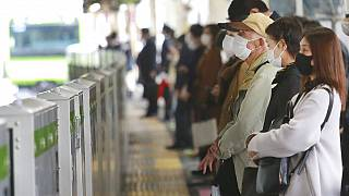 People wearing face masks to protect against the spread of the coronavirus wait for train at a station in Tokyo