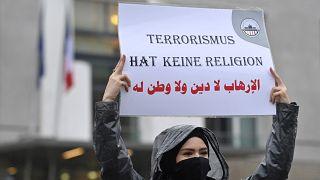 """متظاهر يرفع لافتة كتب عليها """"الإرهاب لا دين له"""" خلال مسيرة لجمعيات فلسطينية وعربية أمام السفارة الفرنسية في برلين، 30 أكتوبر 2020"""
