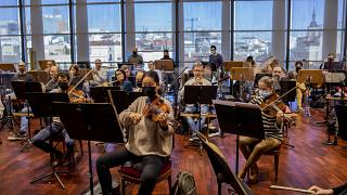 Musicians wearing face masks or behind screens due COVID-19 protocol measures rehearse at the Teatro Real in Madrid, Spain.