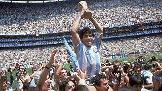 Maradona brandissant le trophée de la Coupe du monde de football, après la victoire de l'Argentine 3-2 sur la RFA, le 29 juin 1986 à Mexico