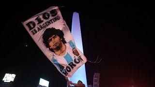 مشجع لكرة القدم يرفع علما يحمل صورة مارادونا في العاصمة الأرجنتينية بيونس آيرس. 2020/11/25