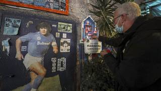 A man in front of a makeshift shrine of soccer legend and former Napoli player Diego Armando Maradona, pays his homage to the late soccer legend, in Naples.